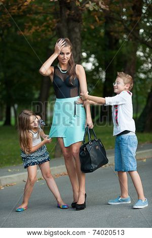 Mother With Naughti Son And Daughter On A Walk In Park