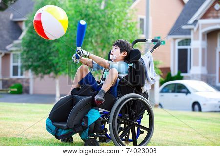 Disabled Boy Hitting Ball With Bat At Park