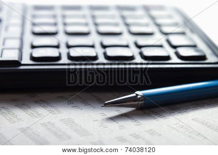 Calculator, pen, document lying on the desk