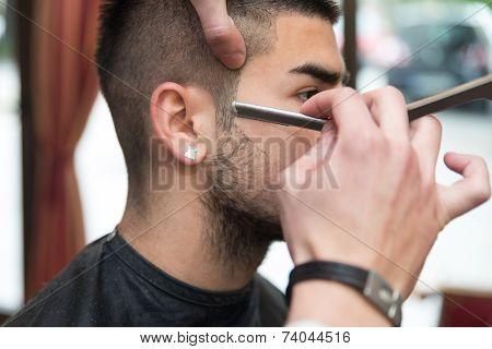 Hairdresser Shaving Man's Chin With A Straight Razor