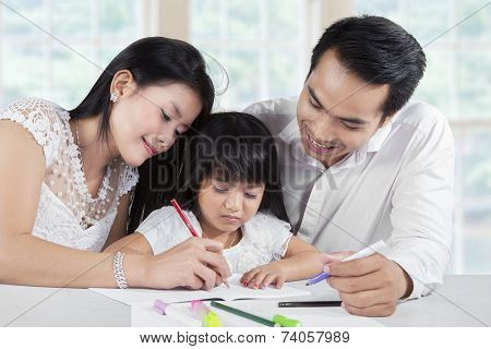 Girl In Homeschooling With Their Parents