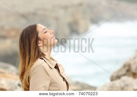 Woman Breathing Fresh Air In Winter On The Beach