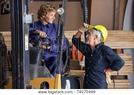 Happy senior carpenter communicating with colleague using forklift in workshop