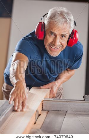 Portrait of senior male carpenter cutting wood with tablesaw in workshop
