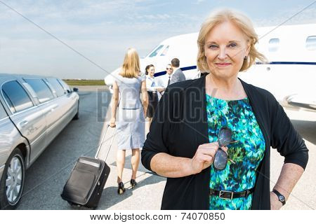 Portrait of confident businesswoman with limousine and private jet in background