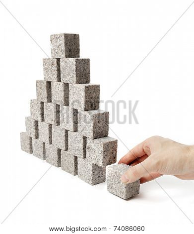 Hand removing the corner stone of a pyramid made of small granite rock blocks.