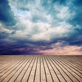 Wooden floor with perspective and stormy colorful cloudy sky poster