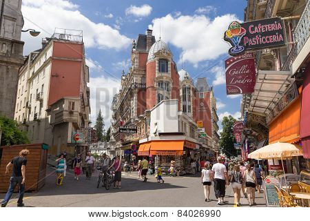 Shoppers And Tourists Wander The Town Centre In Lourdes