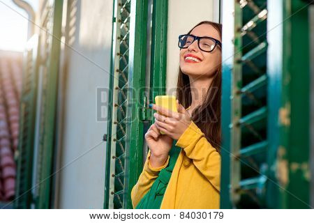 Young woman in yellow sweater and glasses using mobile phone on the balcony with window shutters in old building. poster