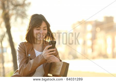 Happy Girl Using A Smart Phone In A City Park