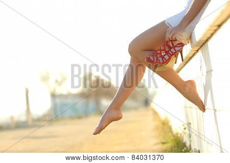 Woman Legs Silhouette With Heels Hanging Of Her Hands