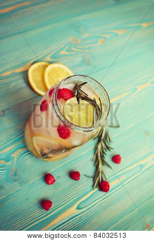 refreshing detox water with fruits in jar on wooden table, toned retro-insta effect poster