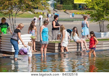 Adults And Children Standing On The Shore Of A Pond