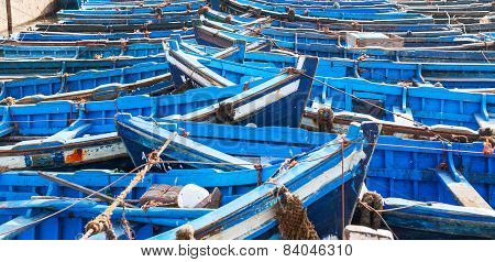 Many blue empty fishing boats tied next to eath other
