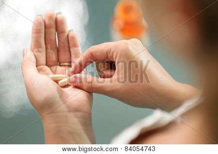 Young Woman Taking Vitamins Ginseng Pill