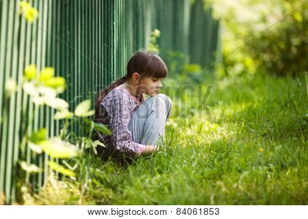 Sad Girl Sitting On The Grass