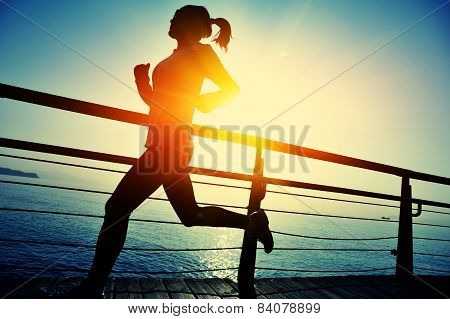 healthy lifestyle sports woman running on wooden boardwalk sunrise seaside