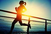 healthy lifestyle sports woman running on wooden boardwalk sunrise seaside poster