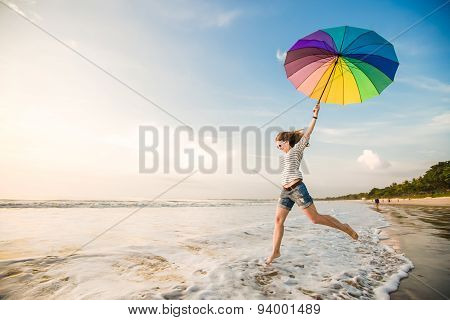 Cheerful young girl with rainbow umbrella having fun on the beach before sunset. Travel, holidays, v
