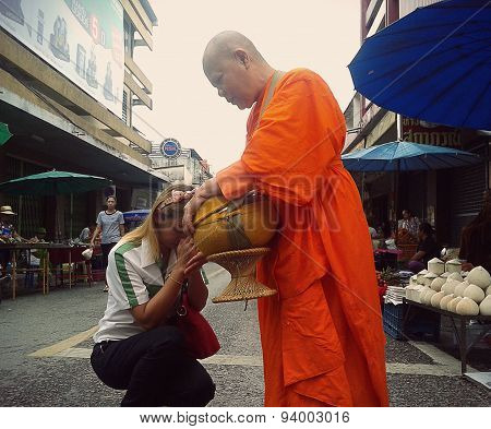 Woman Prays After Giving Alms To Buddhist Nun Phayao, Thailand : June 15, 2015