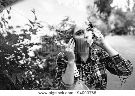 Hipster Girl Enjoying Music On Headphones, And Chewing Gum.