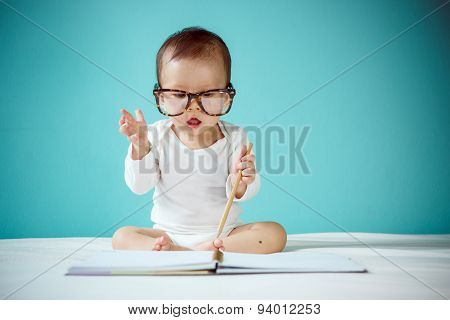 Cute Asian Baby Girl Sitting On Stomach On Bed, Studio Shot