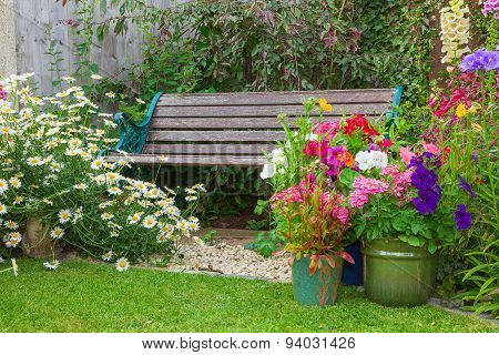 Garden With Bench And Containers Full Of Flowers