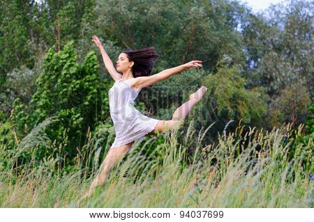 Young Beautiful Ballerina Jumping High In The Air On Sunny Summer Day