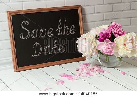 Invitation with bouquet of peonies and chalkboard