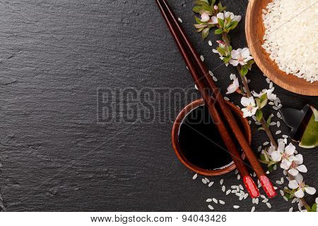 Japanese sushi chopsticks, soy sauce bowl, rice and sakura blossom on black stone background. Top view with copy space poster