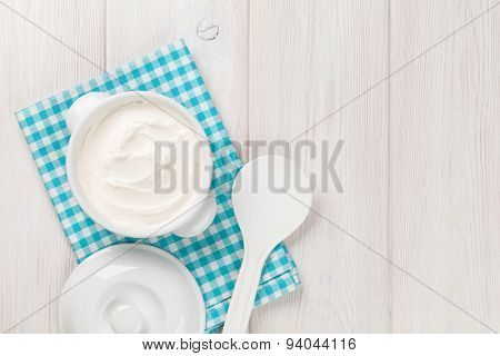 Sour cream in a bowl on wooden table. Top view with copy space