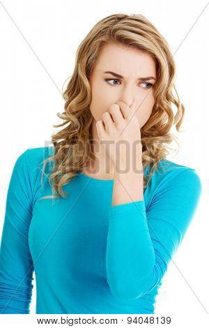 Portrait of a woman clogging nose.