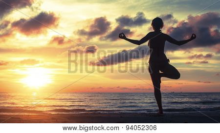 Silhouette of a woman yoga on sea sunset. Healthy lifestyle and fitness concept.