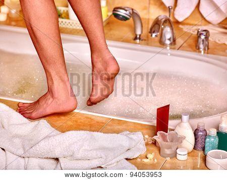 Female  bare feet in bubble bath. Skincare .