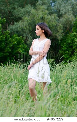 Beautiful Girl On The Green Meadow On Colorful Summer Day