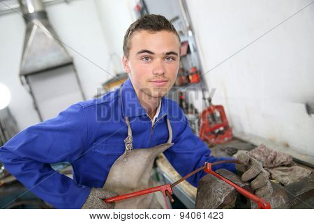 Young man in ironworks training working on steel