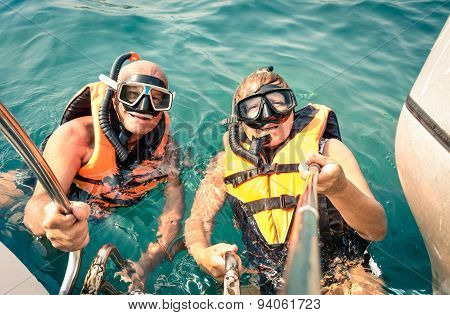 Senior happy couple using selfie stick in tropical sea excursion - Boat trip snorkeling in exotic scenarios - Concept of active elderly and fun around the world - Soft vintage filtered look poster