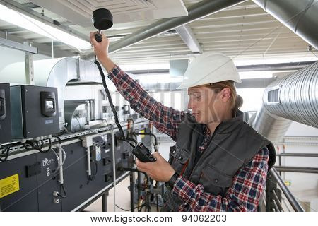 Technician controlling air quality of heating equipment
