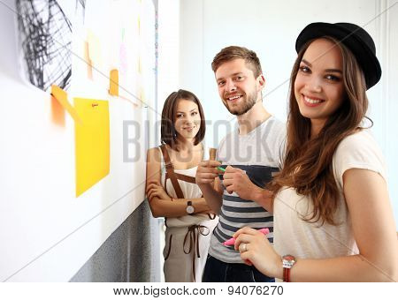 Business, People, Teamwork And Planning Concept - Smiling Business Team With Marker And Stickers Wor