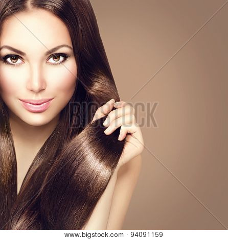 Beauty Model girl with Healthy Brown Hair. Beautiful brunette woman touching her long smooth shiny straight hair. Hairstyle. Hair cosmetics, haircare. Hair care, extensions. Brown background poster