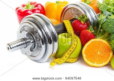 Chrome dumbbells surrounded with healthy fruits and vegetables on a white background.