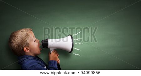 Child speaking through a megaphone against a blackboard with copy space