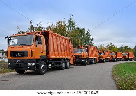 Grodno, Belarus - September 29, 2016: Many new orange garbage trucks on the road in perspective. Grodno, Belarus.