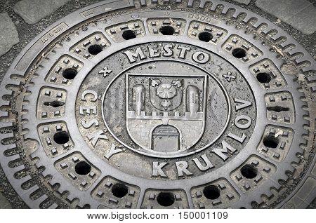 Cesky Krumlov, Czech Republic - April 14, 2016: Wet Metal Manhole cover with the inscription