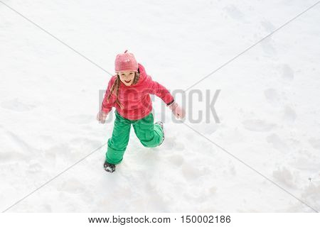 Playful girl with braids playing and running in snow having fun and being active. Natural lifestyle and free childhood concept with copy space.