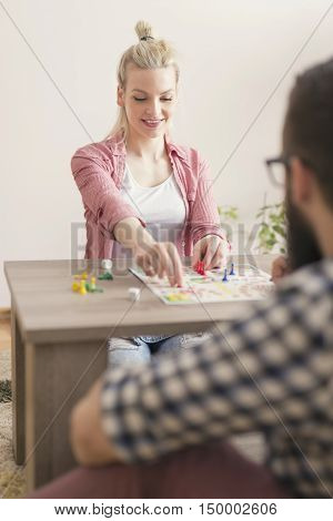 Young couple in love playing ludo board game and having fun. Girl repositioning her figurines on the board
