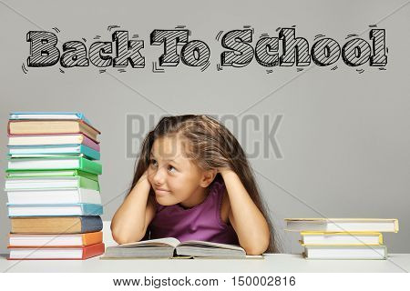 Tired girl looking at big stack of books on table. Text BACK TO SCHOOL on gray background. Education concept.