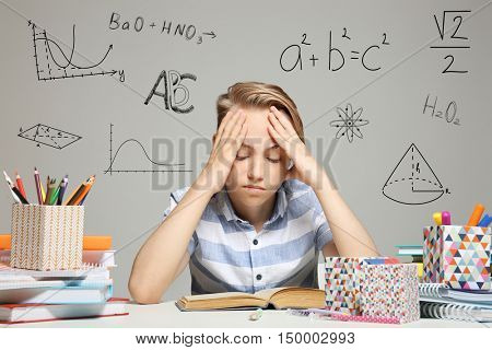 Tired boy studying at table. Different subjects signs on gray background. Education concept.