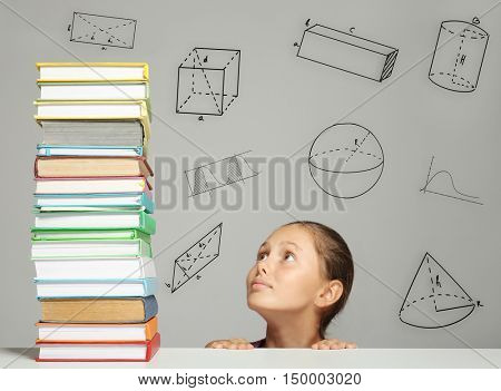 Tired girl looking at big stack of books on table. Geometrical figures on gray background. Education concept.