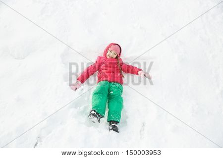 Playful girl with braids playing in snow making a snow angel having fun and being active. Natural lifestyle and free childhood concept with copy space.